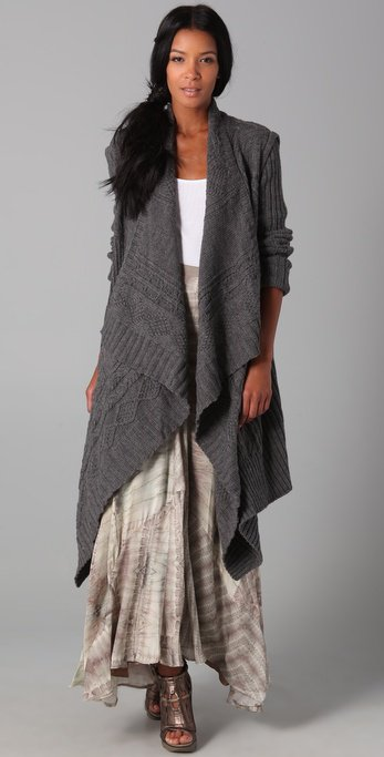 This chunky wool cardigan sweater features a draped shawl collar and ribbed long sleeves