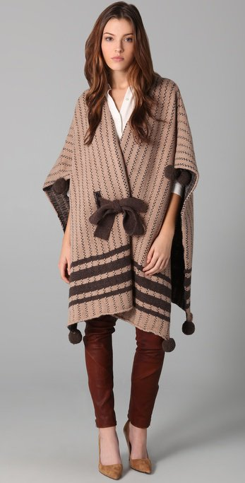 This intarsia-knit wool poncho features a self-belt tie at the waist and button closures at the open sides