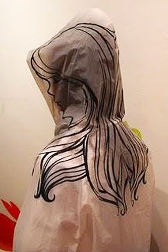 Girl drawing on the hood of a clear raincoat