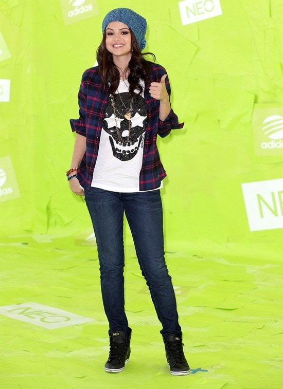 Selena Gomez wore a white skull shirt, blue jeans, blue beanie, black Adidas NEO kicks, and a checkered long-sleeve shirt that she used as a jacket