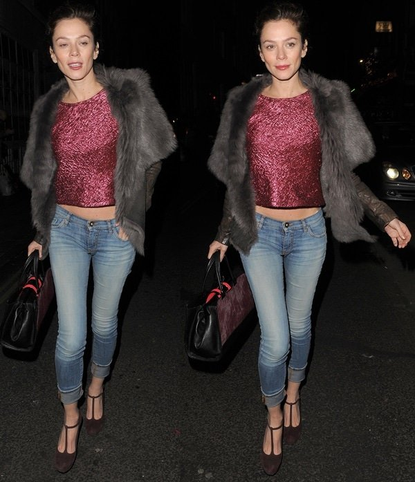 Anna Friel wearing a gray shearling-and-leather jacket worn over a metallic pink cropped top and folded skinny jeans