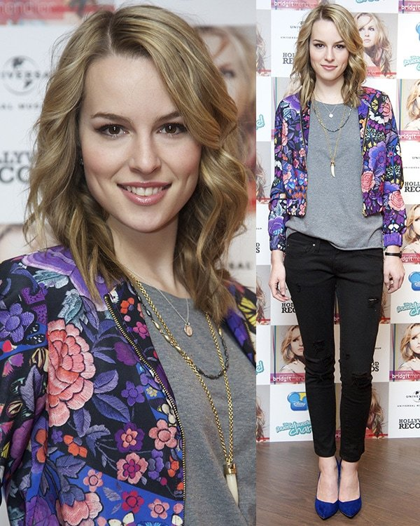 Bridgit Mendler in a purple floral jacket, a gray shirt and black jeans