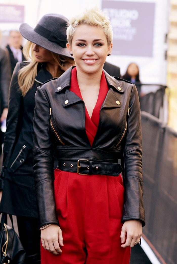 Miley Cyrus rocking a fire red wool belted jumpsuit from the Rachel Zoe Fall 2012 Collection with a Moschino black leather biker jacket