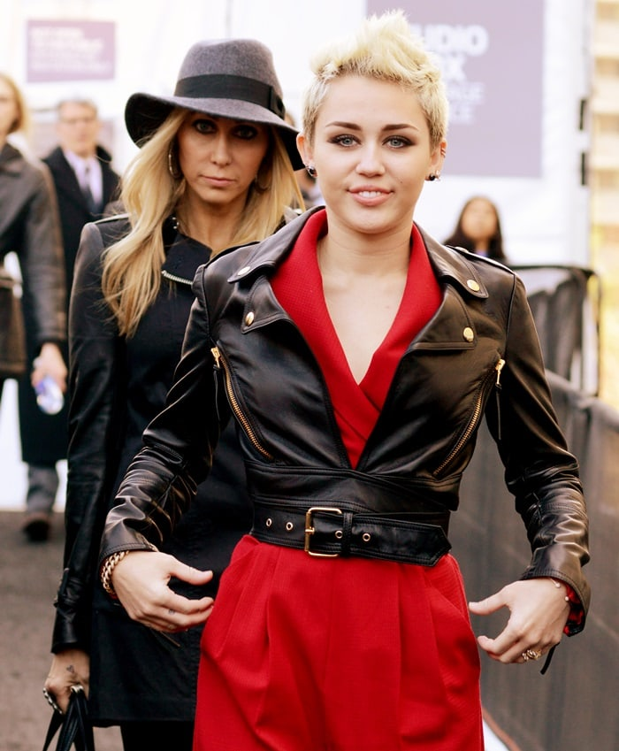 Miley Cyrus decided to toughen up her red Rachel Zoe 'Edith II' jumpsuit with a leather moto jacket from Moschino