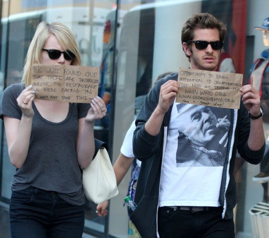 Emma Stone and Andrew Garfield leaving a restaurant after having lunch together, holding handwritten signs promoting organizations they believe in New York City on September 15, 2012