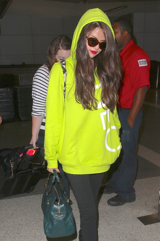 Selena Gomez sporting a neon yellow hoodie from Adidas' fast fashion label NEO