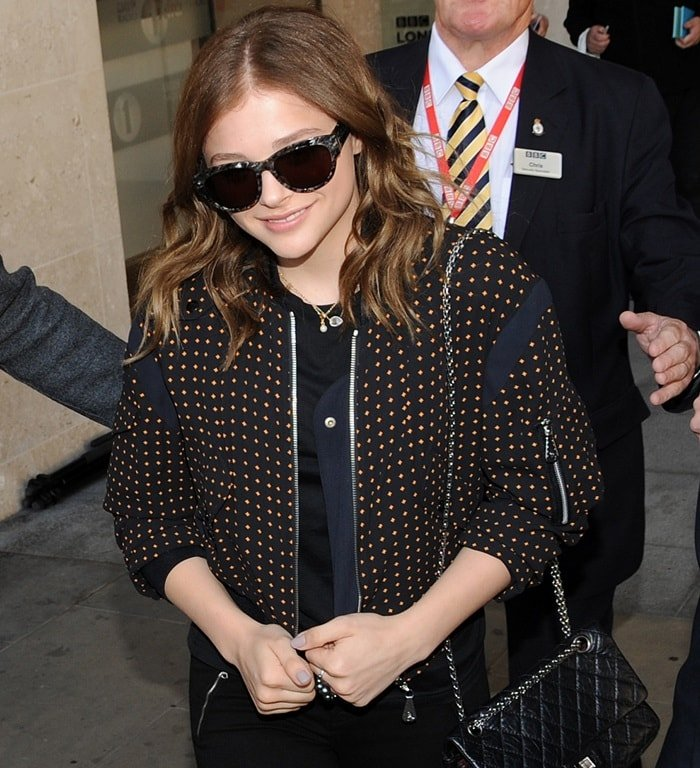 Chloe Moretz covered up with a studded jacket and toted a Chanel handbag for a classic finish