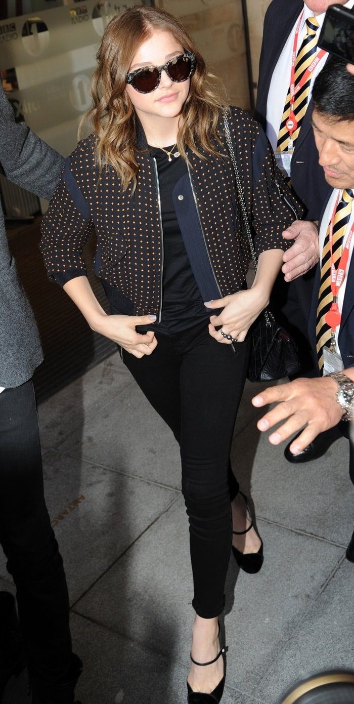 Chloe Moretz wearing an all-black ensemble composed of a black top, black skinny jeans, and black pumps