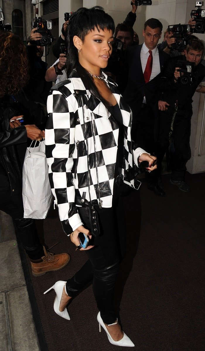 Rihanna wearing a monochromatic ensemble consisting of a Saint Laurent Spring 2014 black-and-white checkered jacket, J Brand skinny jeans, and white Manolo Blahnik pumps