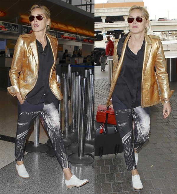 'Basic Instinct' actress Sharon Stone departing from LAX with a friend, wearing a copper-colored jacket, printed trousers, and white shoes in Los Angeles on November 12, 2013