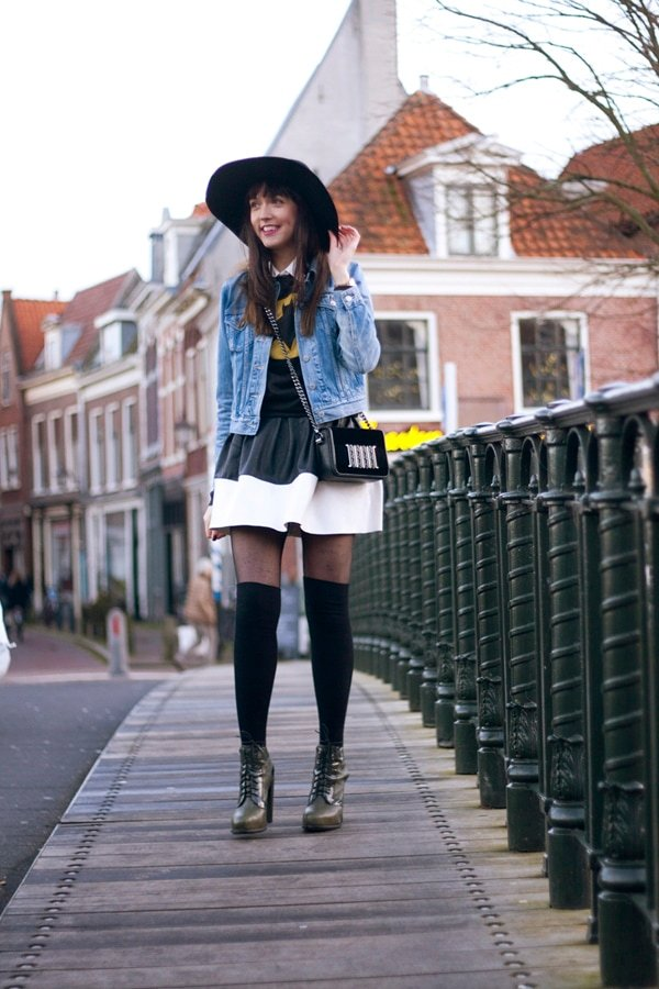 Iris wears a graphic-printed tee and a high-waisted skirt with a denim jacket