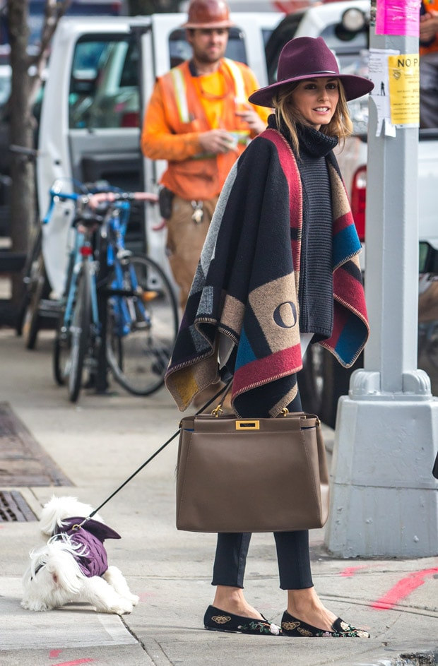 Olivia Palermo looking stylish wearing a hat and a Burberry color block check blanket poncho, running errands in Brooklyn on October 21, 2014