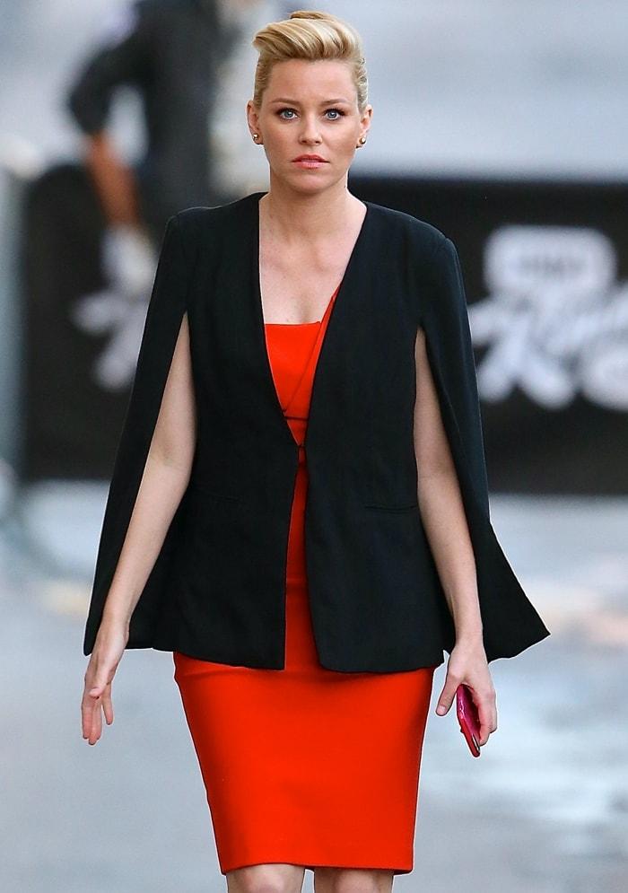Elizabeth Banks wears a black BB Dakota cape blazer over a red Mugler dress