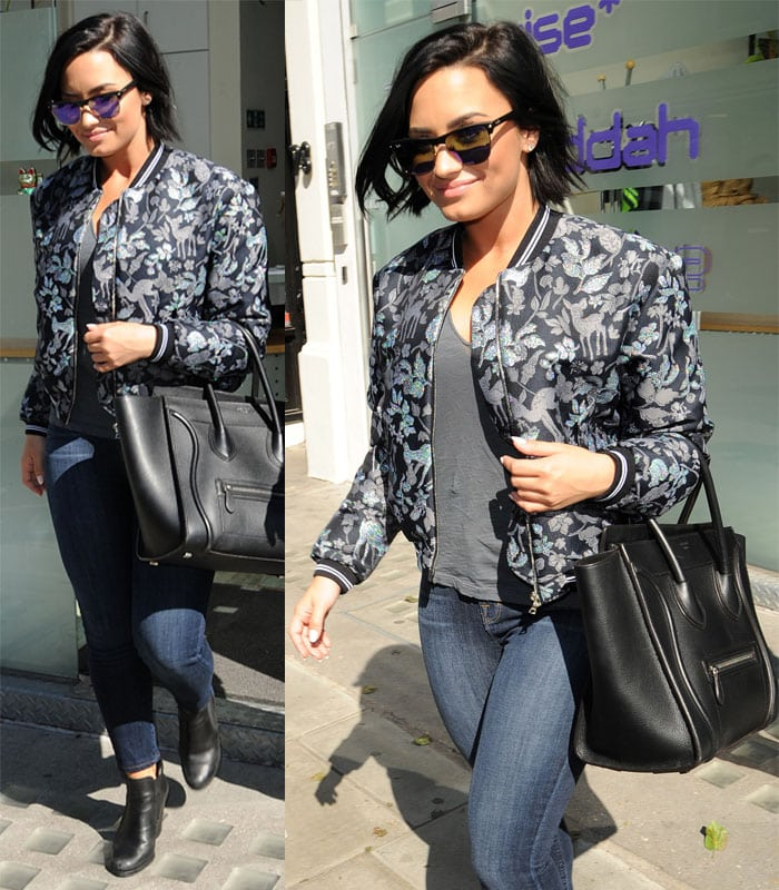 Demi Lovato rocked a casual look comprised of a pair of skinny jeans, a grey shirt, a pair of boots, her trusty Celine 'Boston' bag and a bomber jacket with deer and floral print