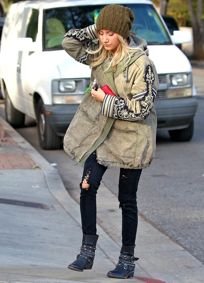 Ashley Tisdale rocked a military jacket with a gray top, black distressed denim jeans, and studded moto boots