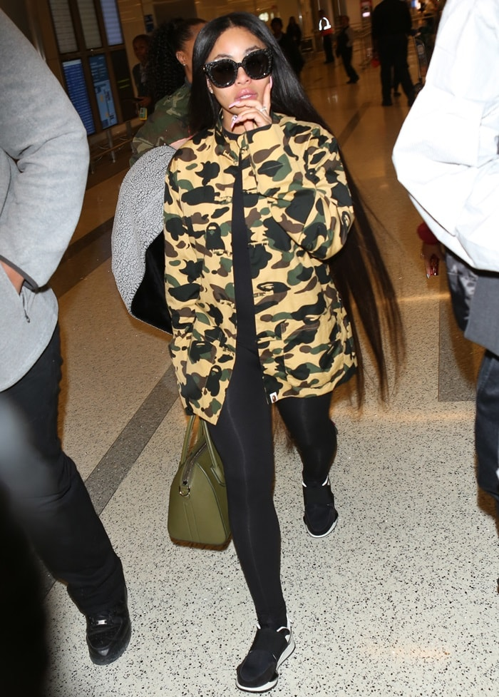 Blac Chyna styled her military jacket with black leggings and black/white sneakers